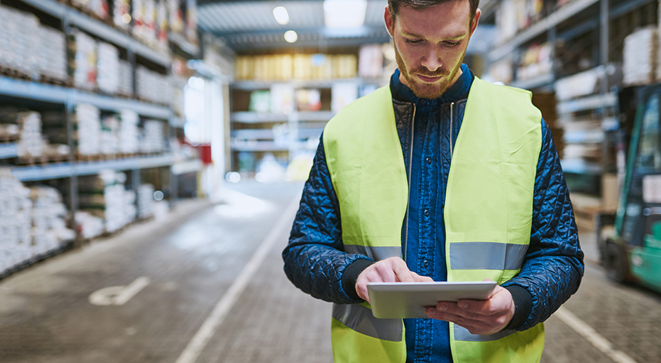 Man wearing vest in warehouse checks warehouse managment system on tablet